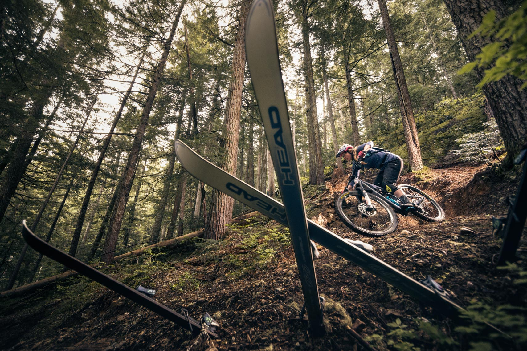 Female mountain bike athlete Sarah Leishman rides past skis