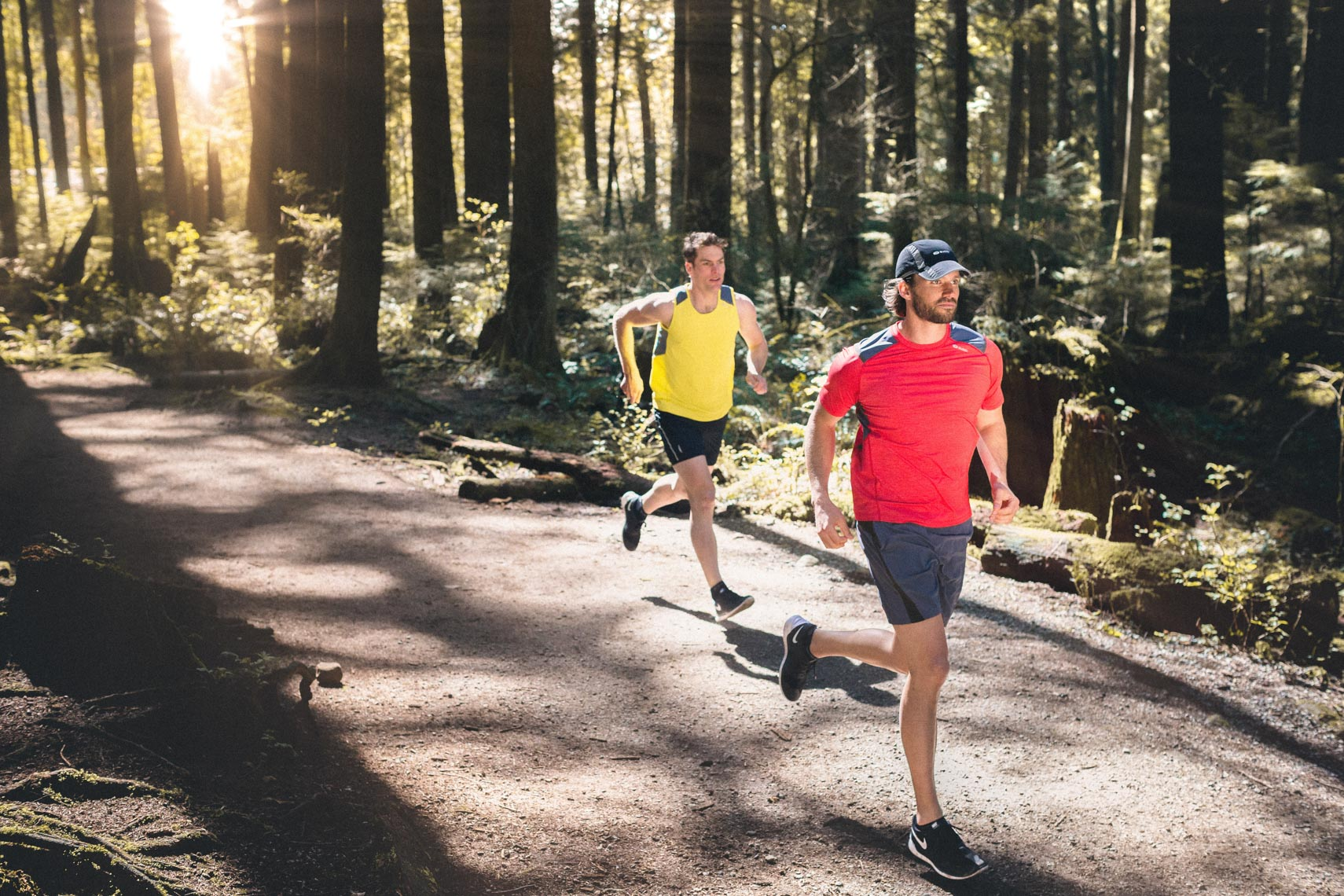 Pair of male joggers in sugoi running apparel in the forest trails of north vancouver