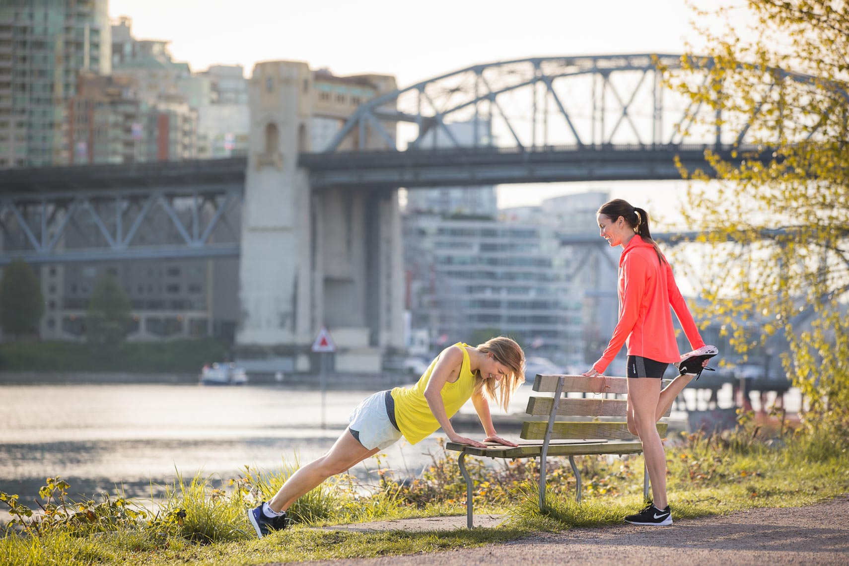 Two girls stretching before jogging near the Burrard Bridge in Vancouver, BC.