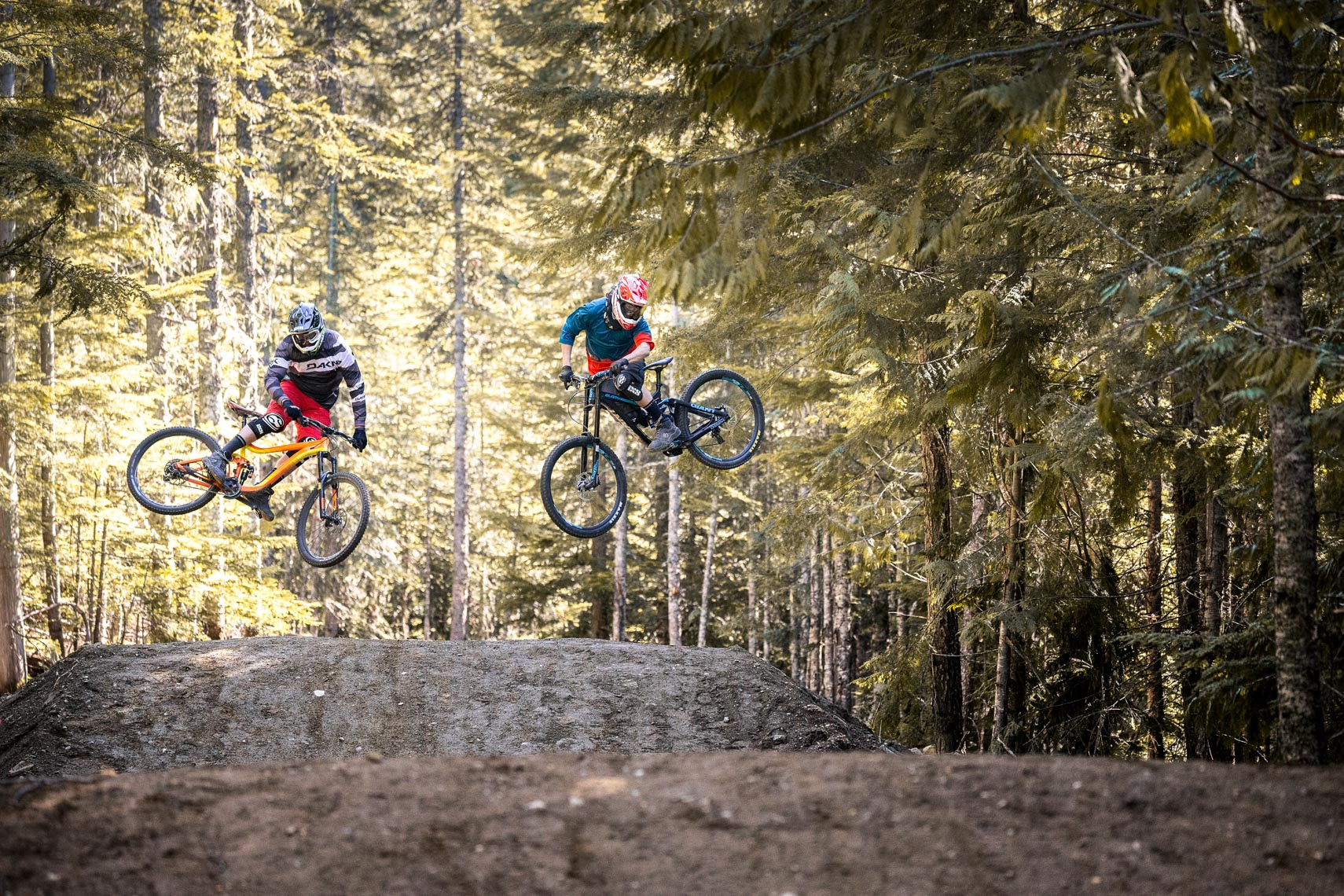 Two mountain bike athletes in the air in the Whistler bike park