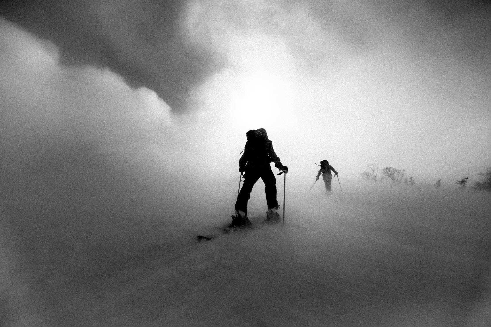 Black and white silhouette ski touring uphill image shot by Whistler ski photographer
