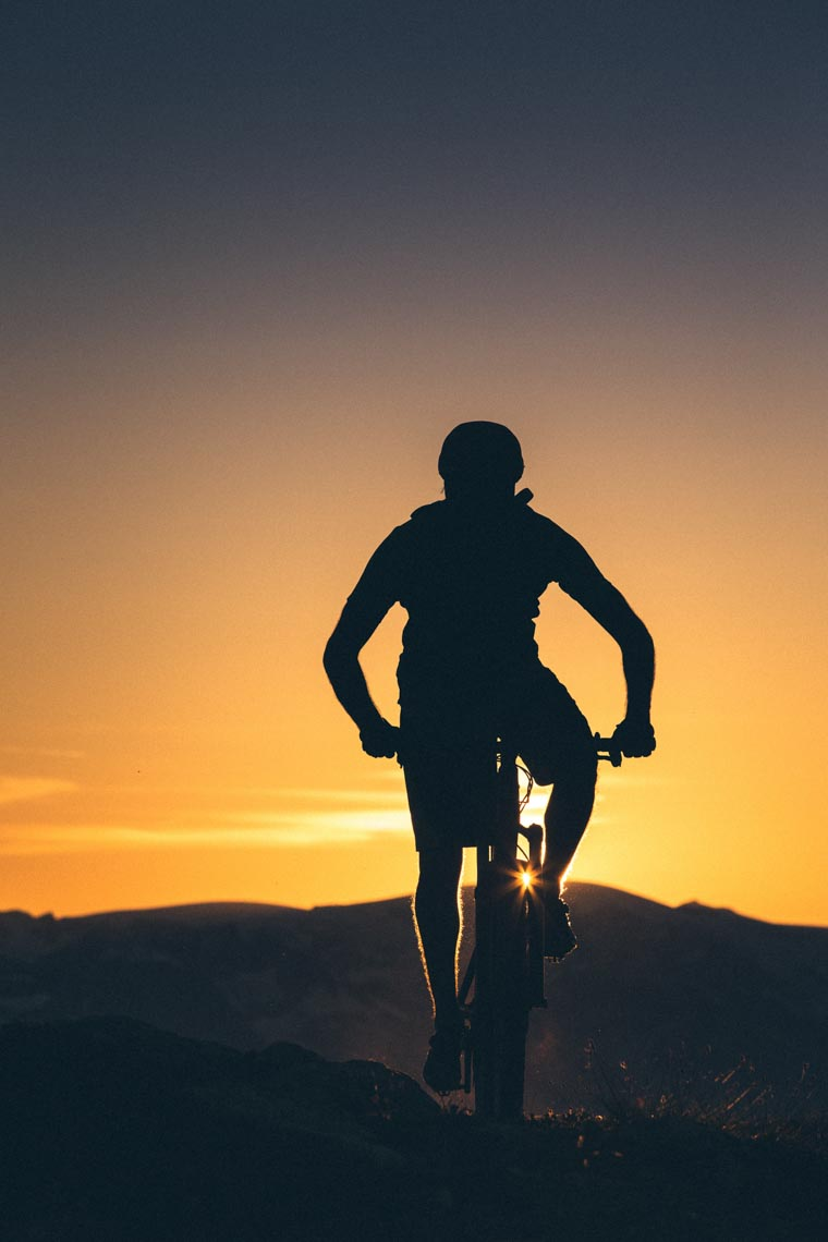 Silhouetted mountain bike athlete at sunset in Whistler, Canada.
