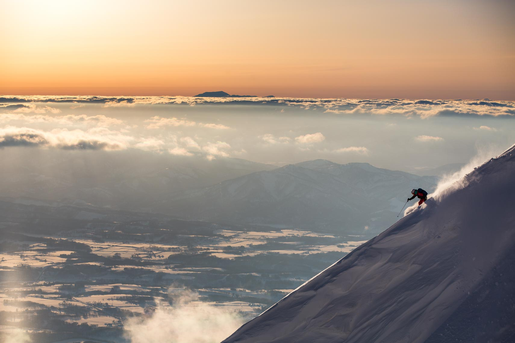 Hakuba ski hill descent at sunset above the clouds