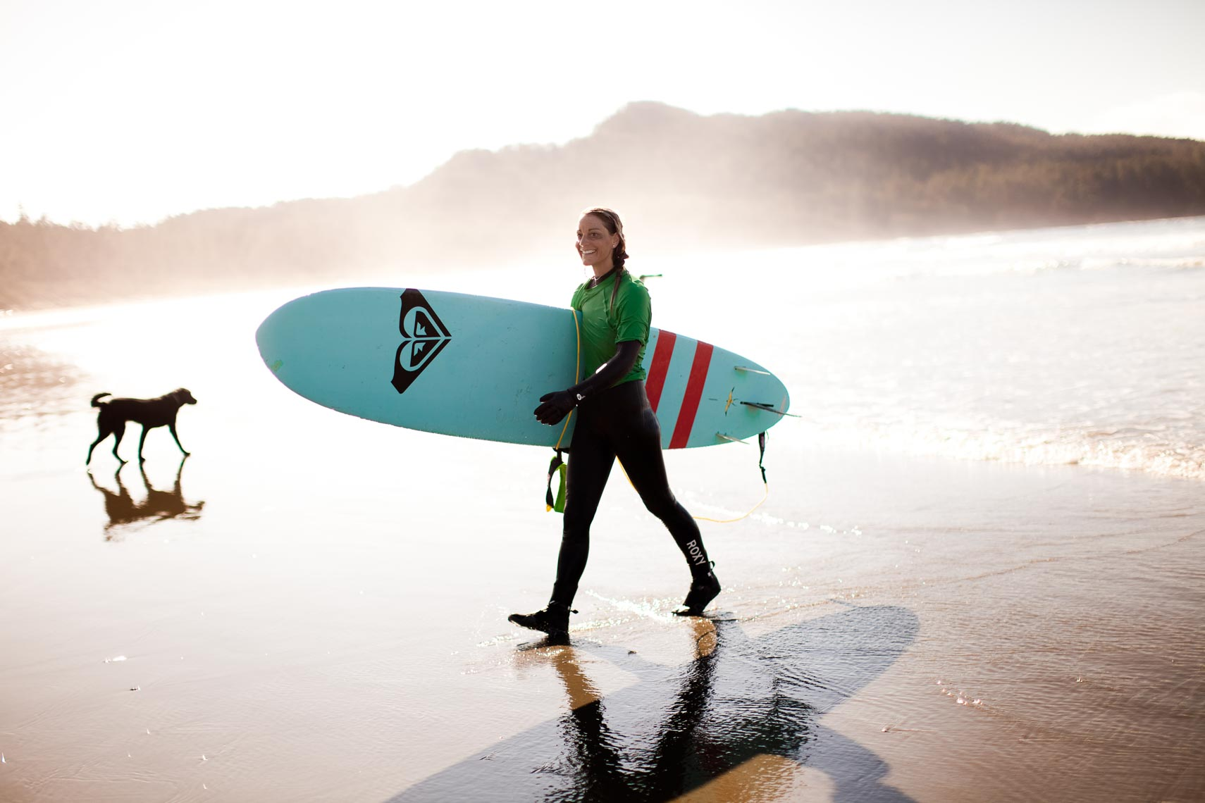 Female surfer walking with surfboard in Tofino, British Columbia, Canada