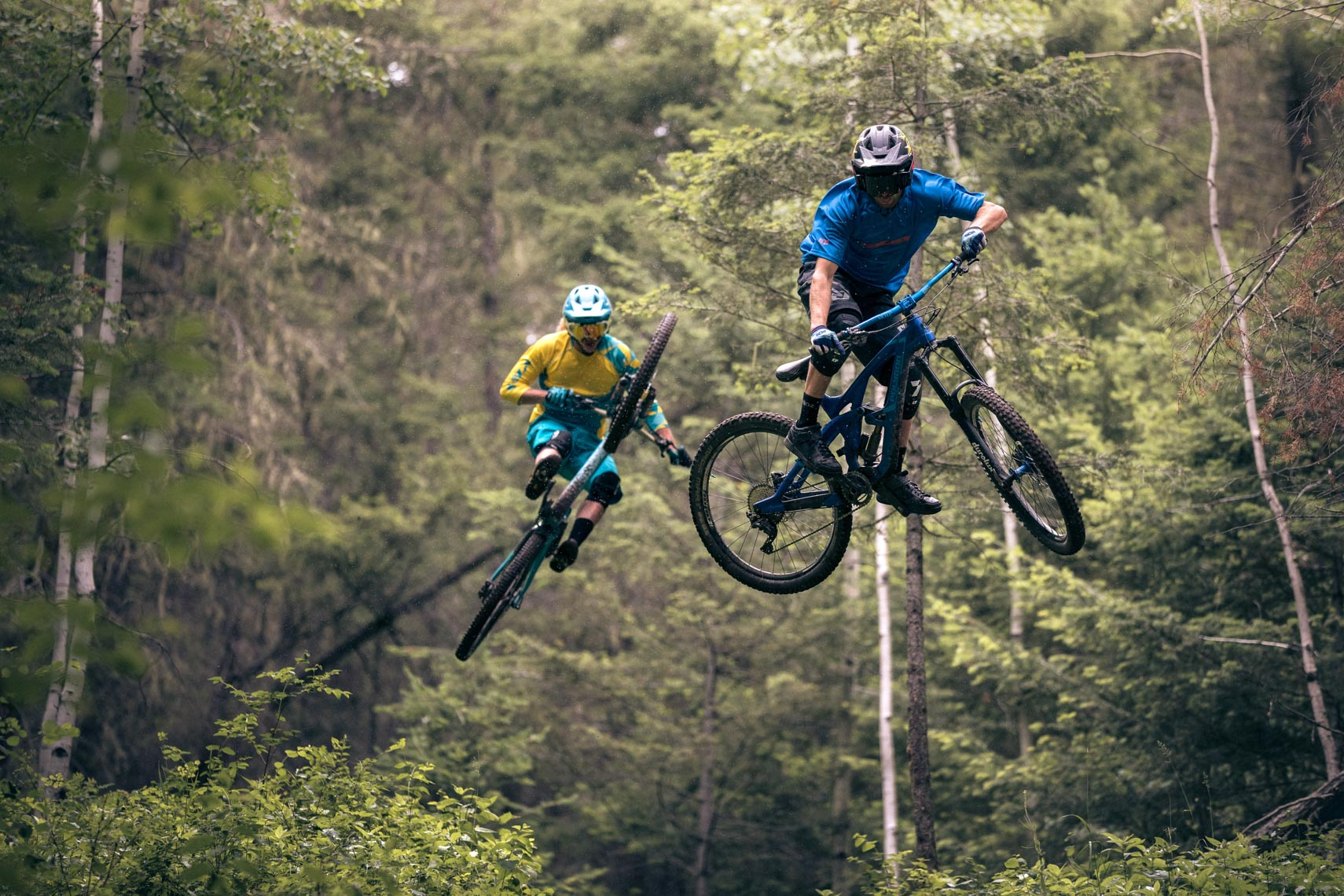 Mountain bike athletes Cody Kelley and Kurt Sorge jump on a trail near Williams Lake BC