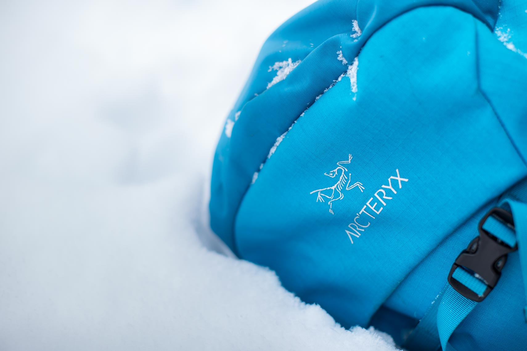 Arcteryx logo on blue backpack in the snow by product photographer