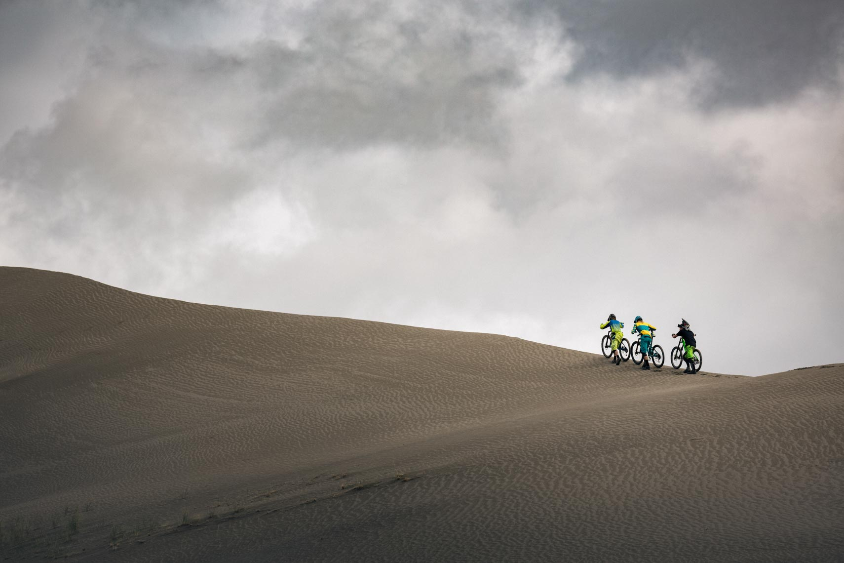 Mountain bike athletes on a sand dune in British Columbia