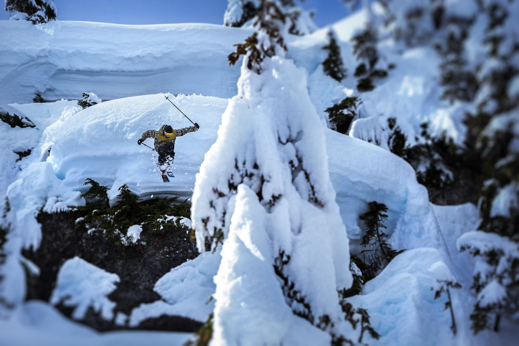 Pro skier drops in Whistler BC Canada shot by ski photographer.