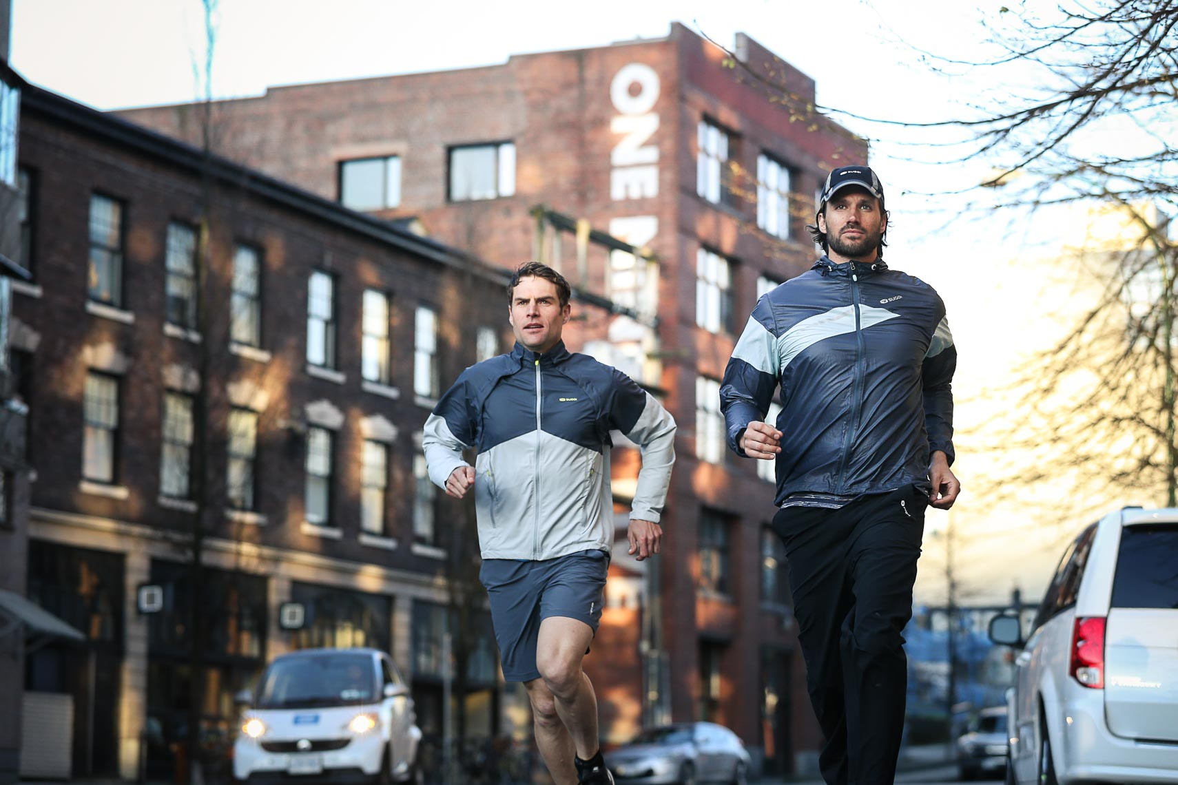 Running athletes in Sugoi jackets in gastown Vancouver by commercial apparel photographer