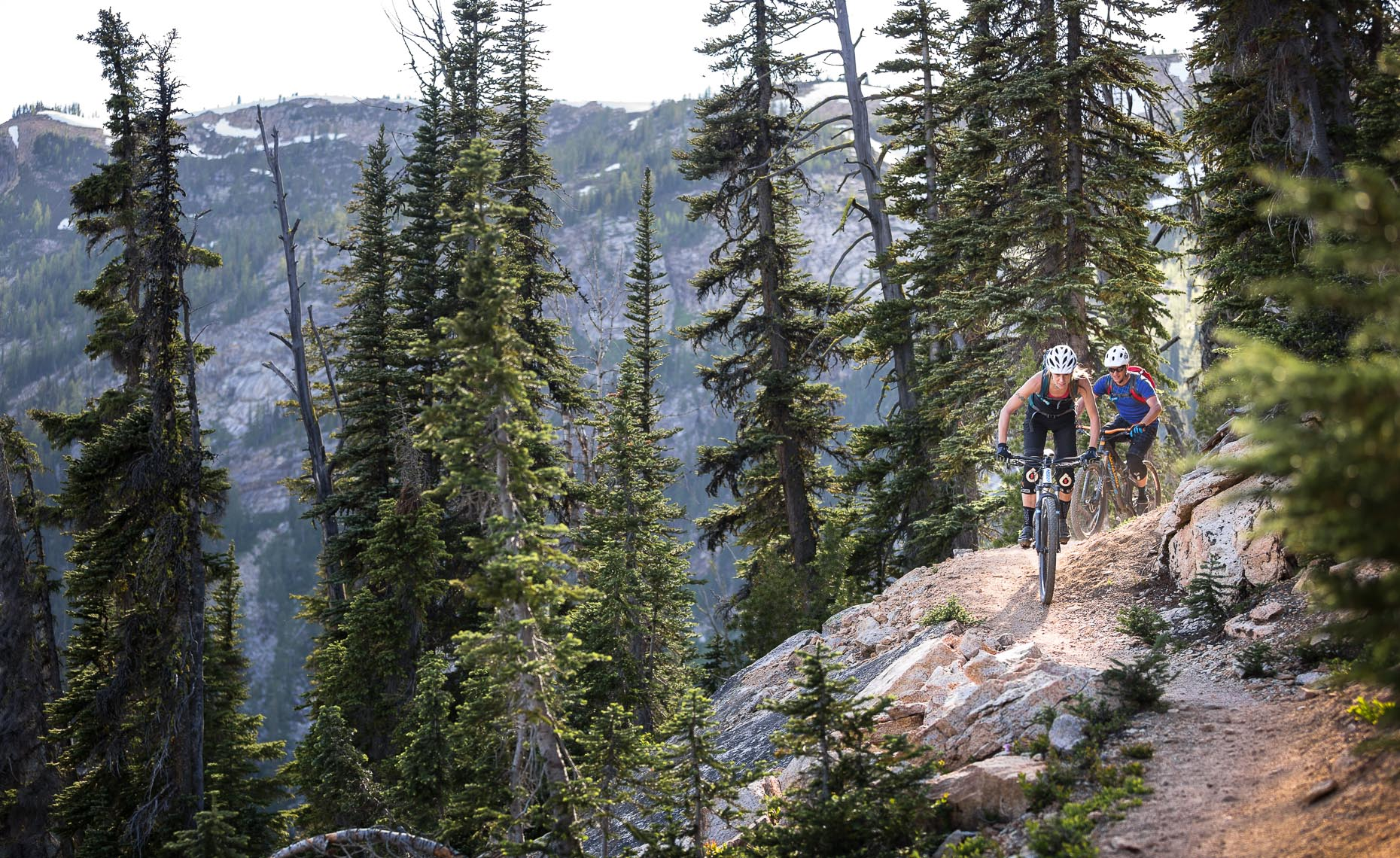 Female mountain biking in the forest and mountains of bc