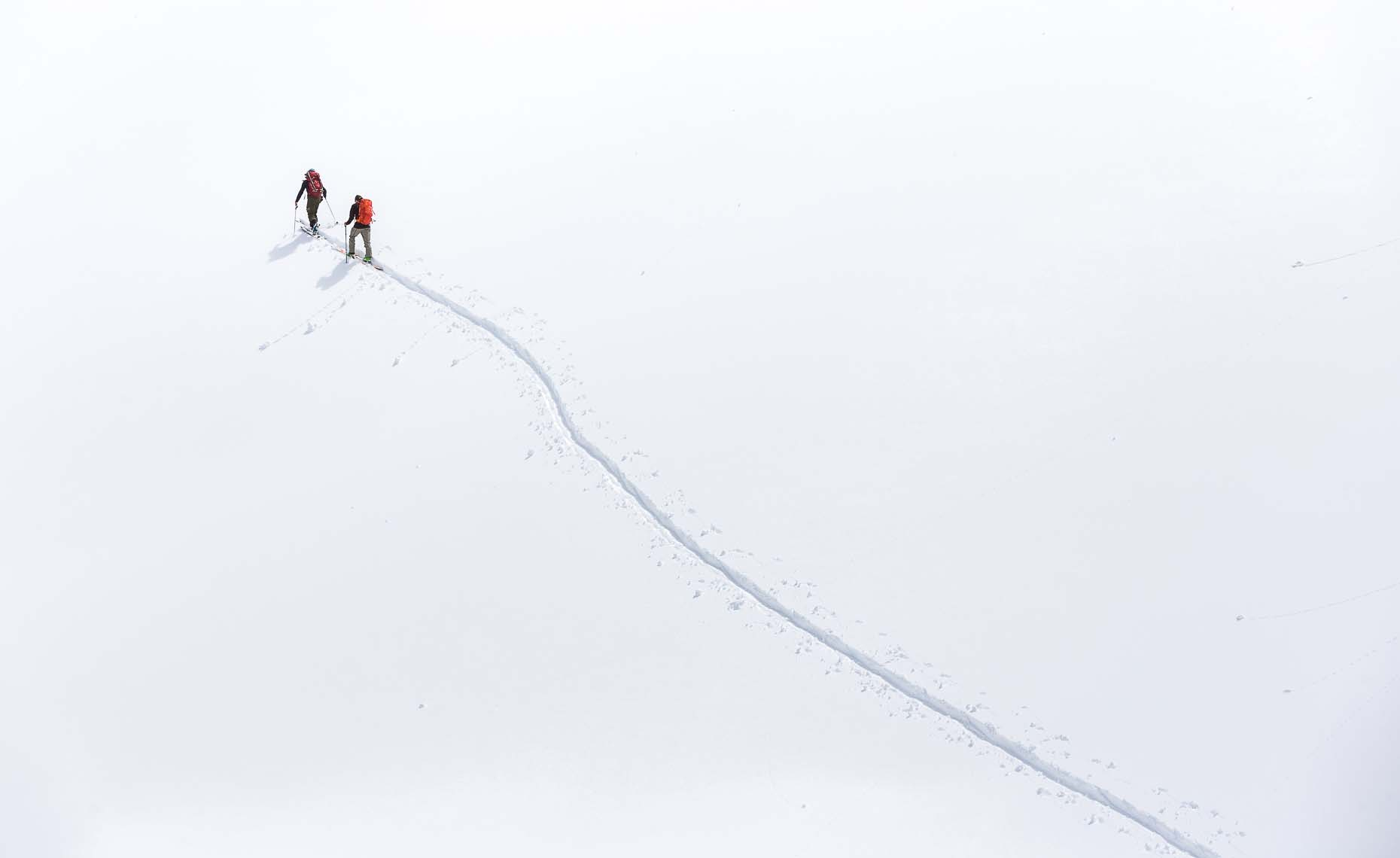 Minimalist ski shot of two skiers hiking up the mountain in Canada.