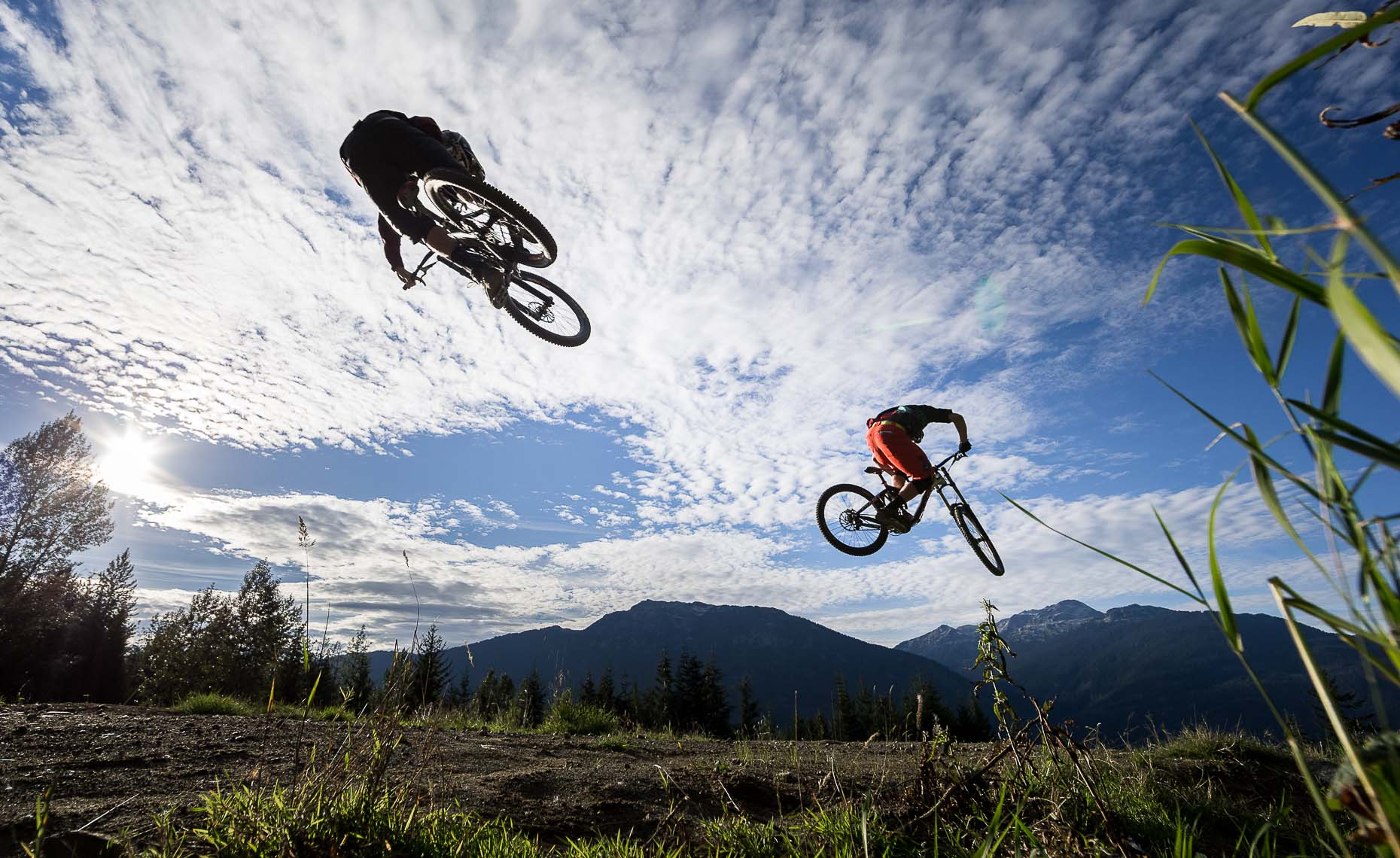 Whistler bike park jump action shot with mountains.