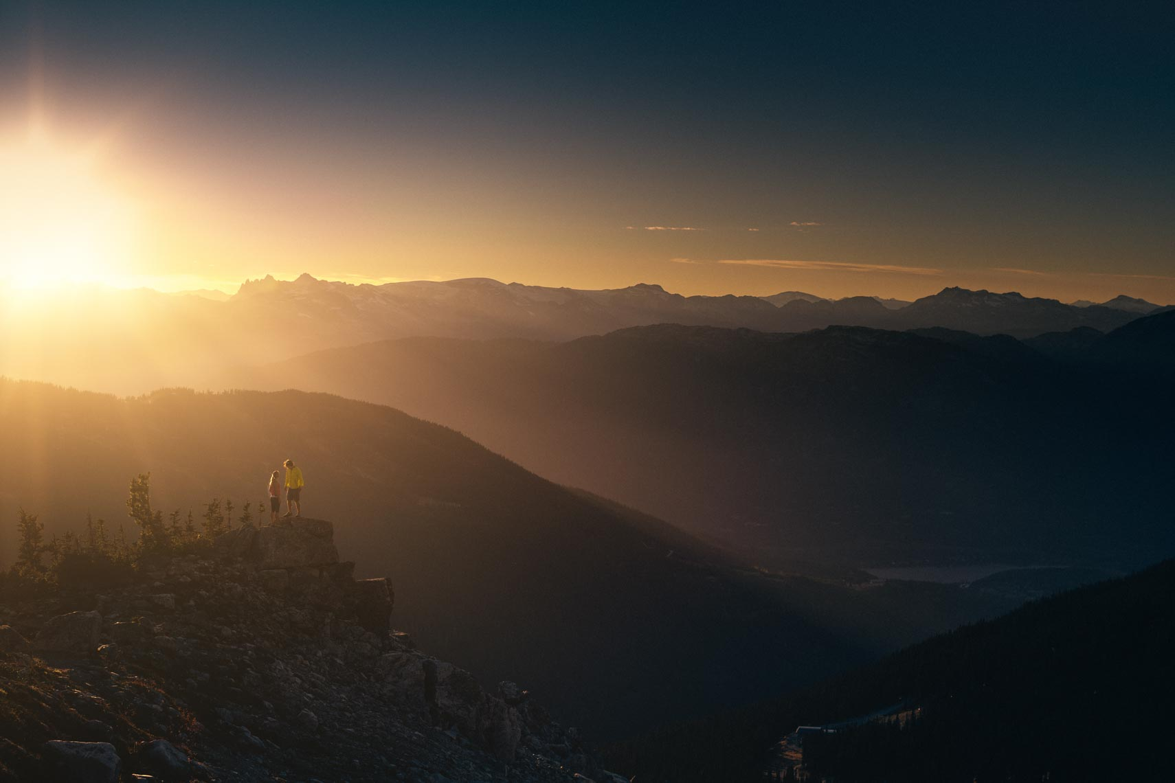 Two hikers at sunset in the mountains of Whistler, British Columbia