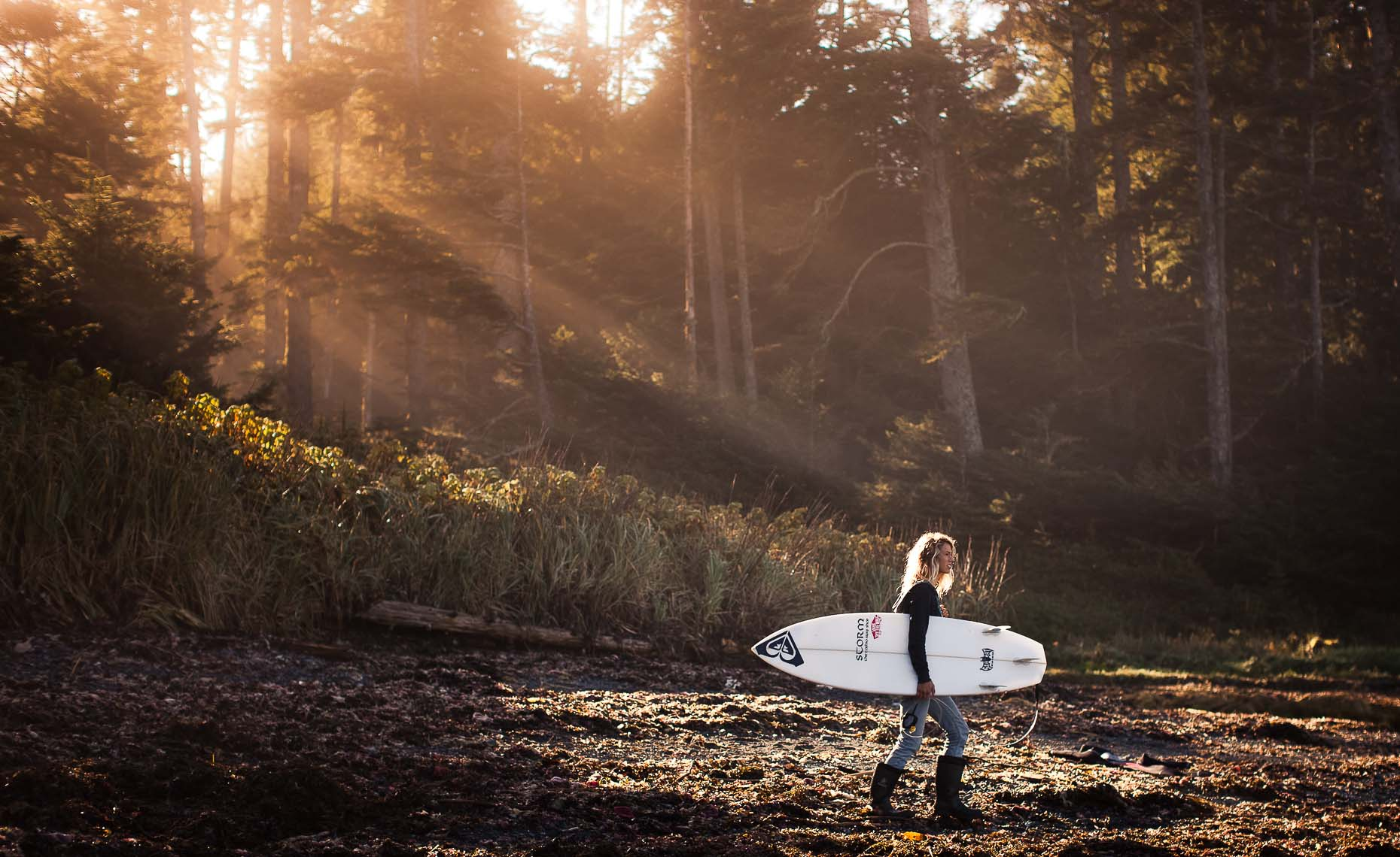 Female surfer with sunbeams in the forest carrying surfboard.
